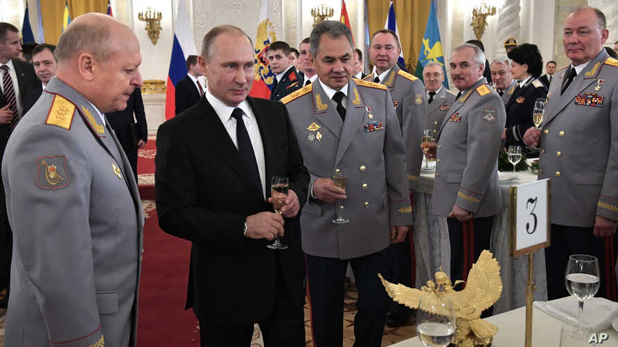 FILE - Russian President Vladimir Putin, second left, and Defense Minister Sergei Shoigu, center, toast with champagne during an awards ceremony for troops who fought in Syria, in the Kremlin, in Moscow, Dec. 28, 2017. Putin says Russia's action in S
