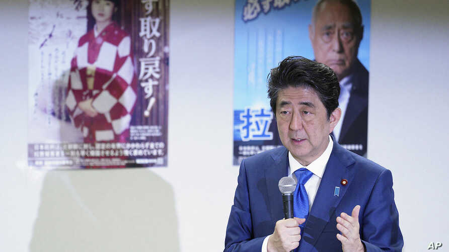 FILE - Japanese Prime Minister Shinzo Abe delivers remarks to families of Japanese citizens abducted by North Korea, in front of abduction awareness posters during an event in Tokyo, Japan, April 22, 2018.