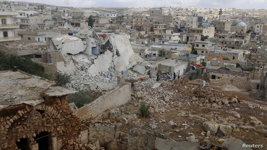 FILE - People inspect a site hit by what residents said were airstrikes carried out by the Russian air force in the town of Darat Izza in the province of Aleppo, Oct. 7, 2015.