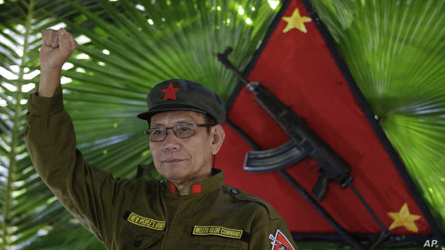 New People's Army new regional rebel commander and spokesman Jaime Padilla, who uses the nom de guerre Comrade Diego, raises his clenched fists after a clandestine news conference in a encampment in the harsh wilderness of the Sierra Madre mountains