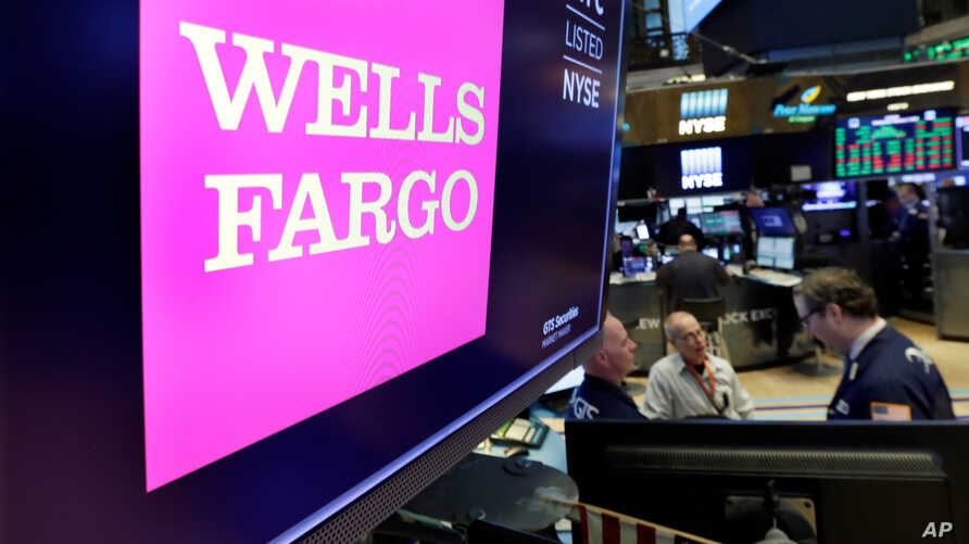 FILE - The Wells Fargo logo appears above a trading post on the floor of the New York Stock Exchange, Feb. 7, 2018.