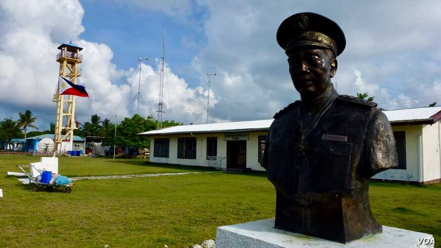 The main town hall of Kalayaan on Thitu Island with the bust of Tomas Cloma, the Filipino marine educator a nd entrepreneur who reportedly discovered the Kalayaan Group of Islands. The lone tower is also seen in the background. (D. Agnote for VOA)