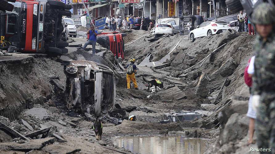 Rescue personnel survey the wreckage after an explosion in Kaohsiung, southern Taiwan, August 1, 2014.