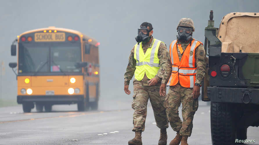 Hawaii National Guard soldiers wear masks to protect themselves from volcanic gases during ongoing eruptions of the Kilauea volcano in Hawaii, May 17, 2018.