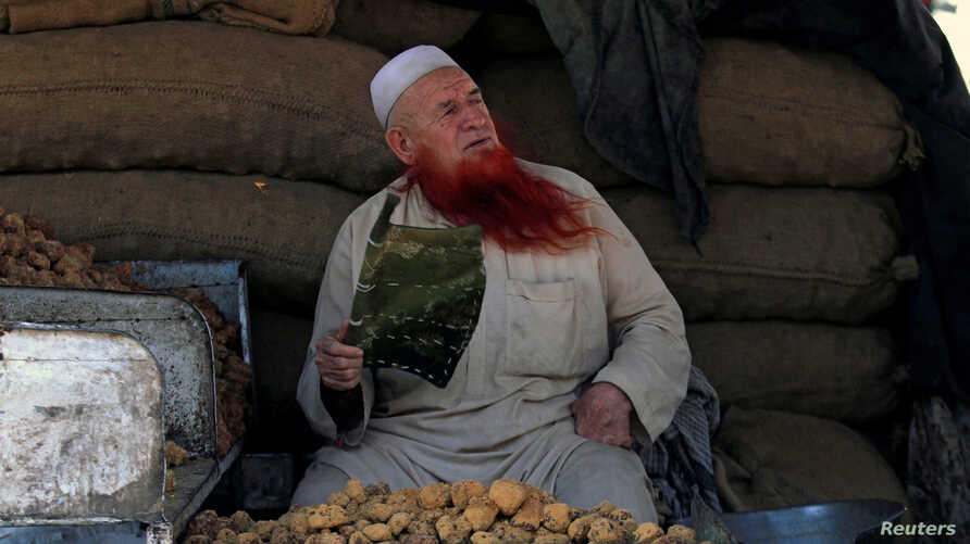 A man sporting a henna-dyed beard fans himself as he sells lumps of brown sugar at the market in Peshawar, Pakistan June 30, 2017.