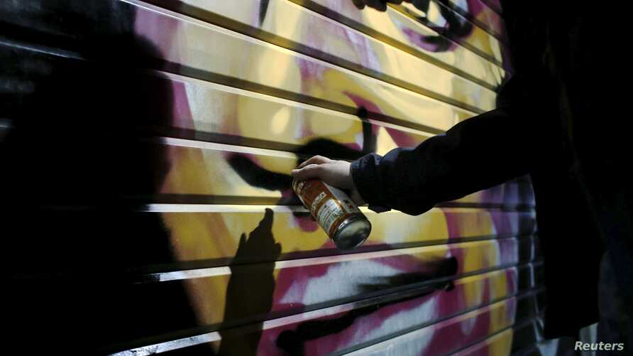 Artist Solomon Souza,22, spray-paints a portrait on the metal shutter of a closed storefront in Mahane Yehuda, one of Jerusalem's most popular outdoor markets, Feb. 24, 2016.