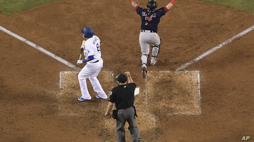Home plate umpire Jeff Nelson makes the call while Boston Red Sox catcher Christian Vazquez celebrates as Los Angeles Dodgers' Manny Machado strikes out to end Game 5 of baseball's World Series against the Los Angeles Dodgers, Oct. 28, 2018, in Los A