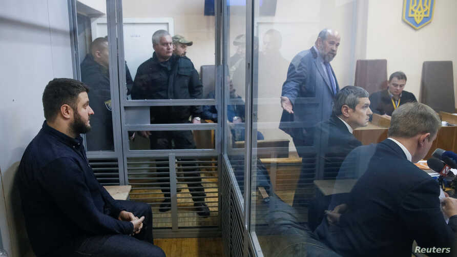 Son of Ukrainian Interior Minister Arsen Avakov, Oleksandr Avakov, left, who is under investigation over suspected corruption, is seen inside a defendant's cage during a court hearing in Kyiv, Ukraine, Nov. 1. Ukrainian investigators fear corruption