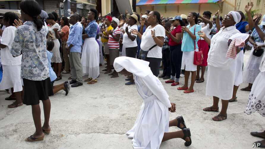 A Catholic nun kneels in prayer during a pause in a procession marking the feast of Corpus Christi in Port-au-Prince, Haiti, May 26, 2016. A review of last year's contested presidential and legislative elections is to be released Sunday.