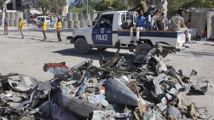A police vehicle drives past wreckage after a suicide car bomb attack on a government building in Mogadishu, Somalia, March 23, 2019.  Al-Shabab gunmen stormed the government building after a suicide car bombing.