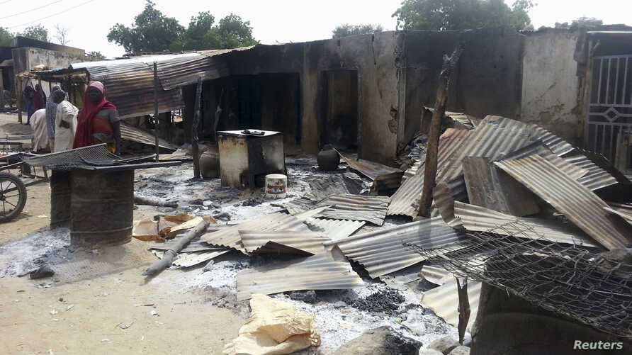 FILE - Residents stand in front of destroyed properties and houses following an attack in Kawuri. An attack by suspected Islamist Boko Haram insurgents on the northeast Nigerian village of Kawuri.