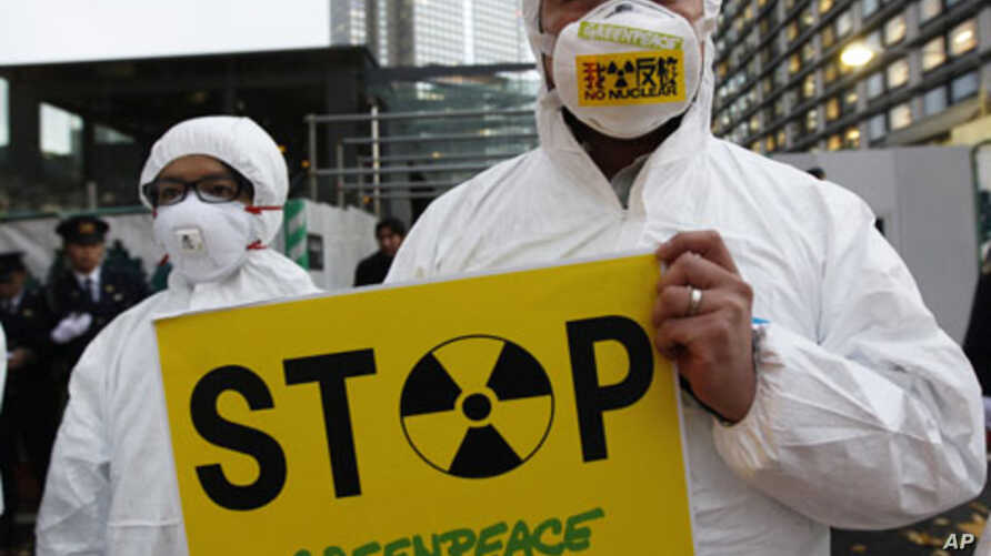 A Greenpeace activist holds a placard during a demonstration outside Japan's Prime Minister Yoshihiko Noda's official residence in Tokyo, criticizing the government's declaration of cold shutdown at the Fukushima nuclear power plant December 16, 2011