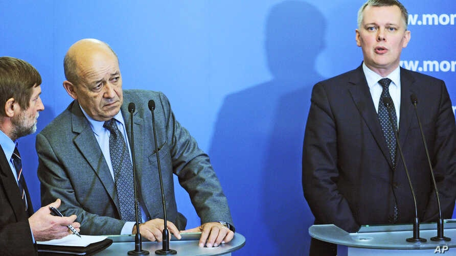 Defense Minister of France, Jean-Yves Le Drian, second left, listens to a translator during a press conference with his Polish counterpart Tomasz Siemoniak, right, in Warsaw, Poland, Nov. 25, 2014.