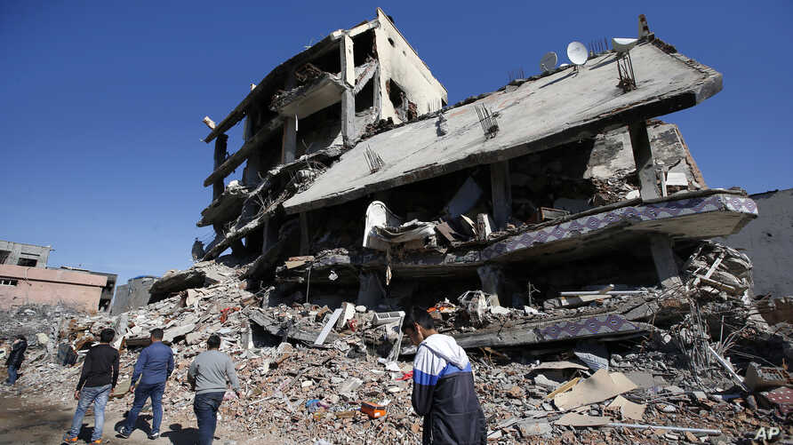 People walk past ruined buildings in Cizre, Turkey, early Wednesday, March 2, 2016.