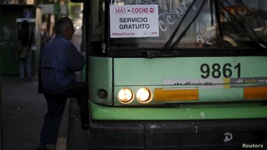 """A passenger boards an electric bus displaying a sign that reads """"MasXCoche. Free Service"""" in Mexico City, Mexico, April 5, 2016."""