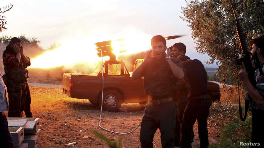 Free Syrian Army fighters fire a rocket towards a castle where pro-government forces are based, in Haram town, Idlib Governorate, October 28, 2012.