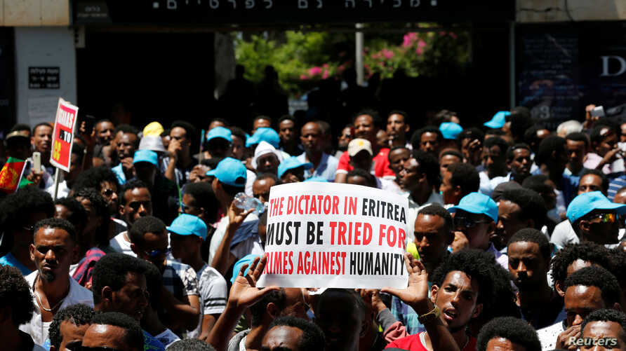 FILE - Eritrean refugees hold placards during a demonstration in support of a recent U.N. report that accused Eritrean leaders of committing crimes against humanity, outside the E.U. offices in Ramat Gan, Israel, June 21, 2016.