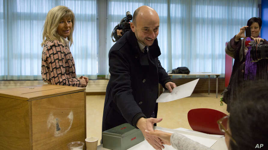 Socialist Party head Etienne Schneider, center, shakes hands with registrars at a polling station prior to casting his vote in Luxembourg on Sunday, October 20, 2013.