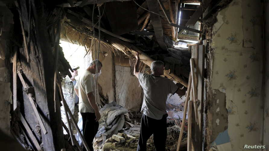 Residents remove debris inside a damaged building, which according to locals was caused by recent shelling, in Avdiivka in the Donetsk region, Ukraine, July 18, 2015.