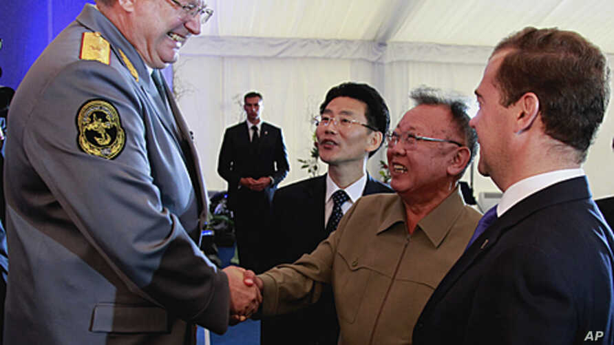 North Korean leader Kim Jong Il shakes hands with chief conductor of the main orchestra of the Defense Ministry, Viktor Yeliseyev, left, as Russian President Dmitry Medvedev smiles in Siberia's Buryatia region, August 24, 2011