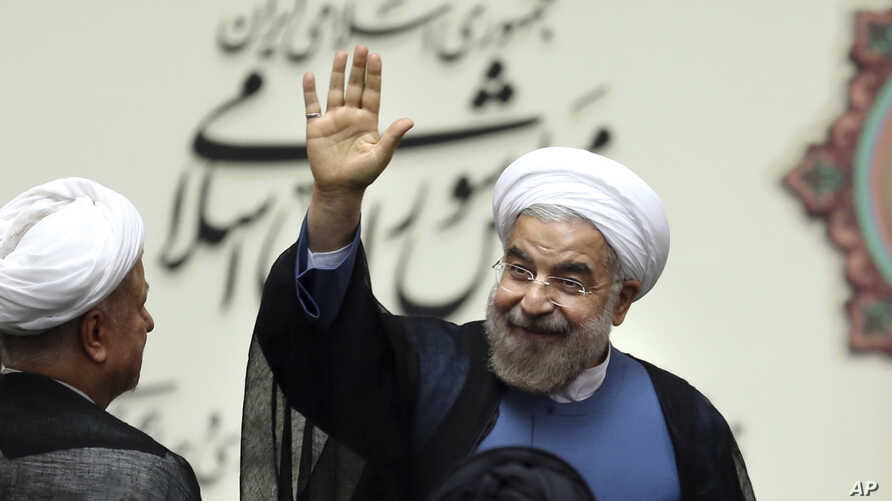 Iran's new President Hassan Rouhani, waves after swearing in at the parliament, in Tehran, Iran, Aug. 4, 2013.