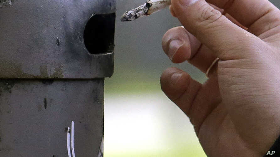 FILE - A smoker discards a cigarette into a container at a designated smoking location in Seattle, Wash., Oct. 17, 2015.