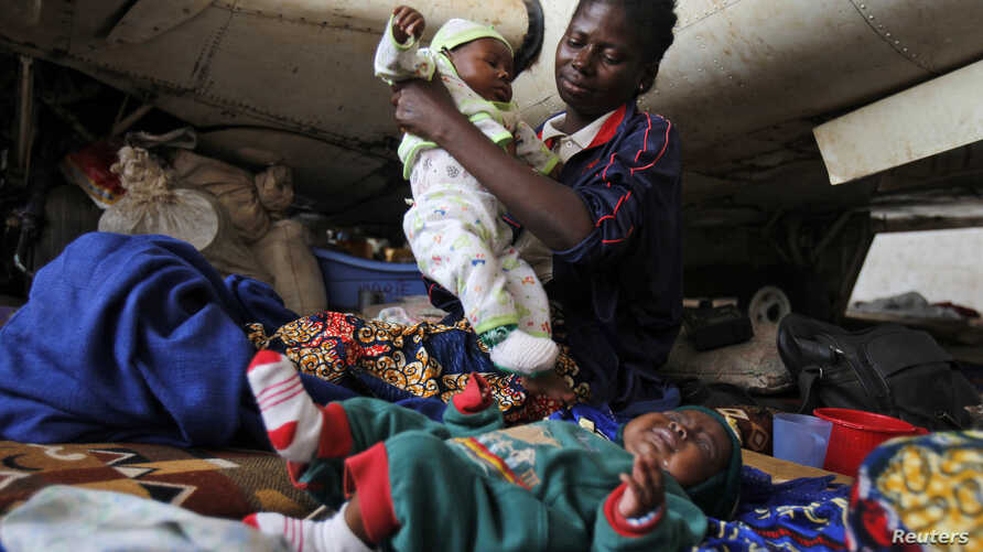 A Central African woman displaced by inter-communal violence takes care of her twin baby boys at a camp for displaced persons at Bangui M'Poko International Airport, Feb. 11, 2014.