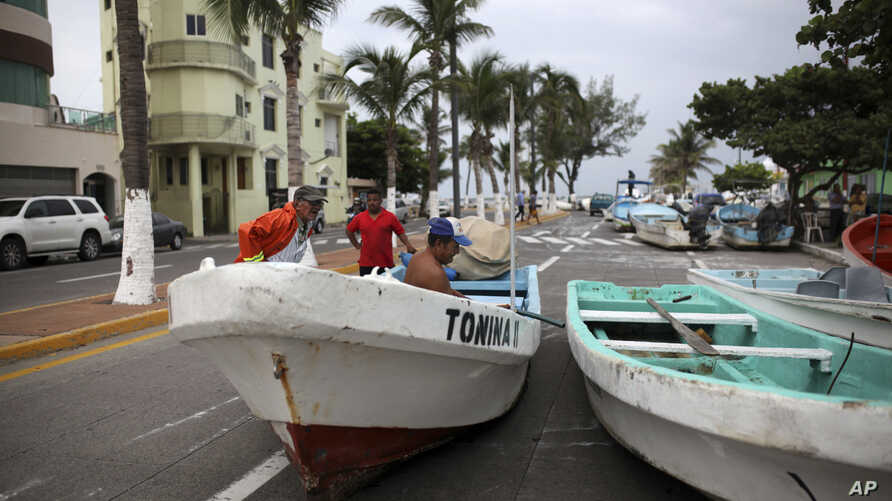 Fishermen move their boats, normally moored in the Gulf of Mexico, onto a coastal road to protect them ahead of the arrival of Tropical Storm Franklin, in the port city of Veracruz, Mexico, Aug. 9, 2017.