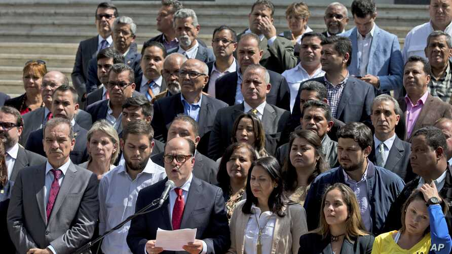 Venezuela's National Assembly President Julio Borges, center, surrounded by fellow legislators, speaks during a meeting with the media, in Caracas, Venezuela, April 18, 2017.