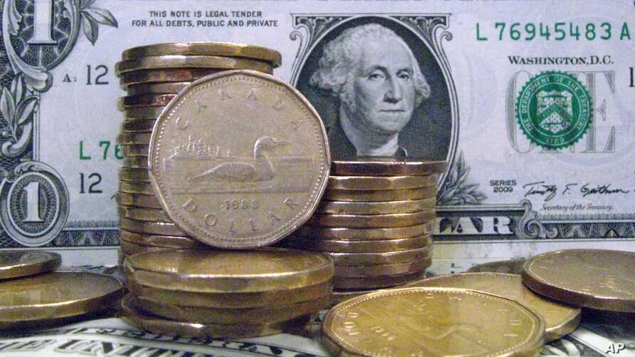 """Canadian dollar coins, also known as """"loonies,"""" are posed with U.S dollar bills Tuesday, April 6, 2010, in Montreal."""