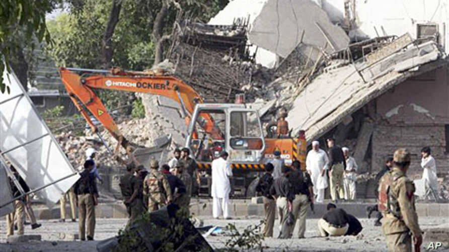 Pakistani soldiers, police officers check a police building after it was attacked by a suicide bomber in an explosives-laden pickup truck in Peshawar, Pakistan, May 25, 2011