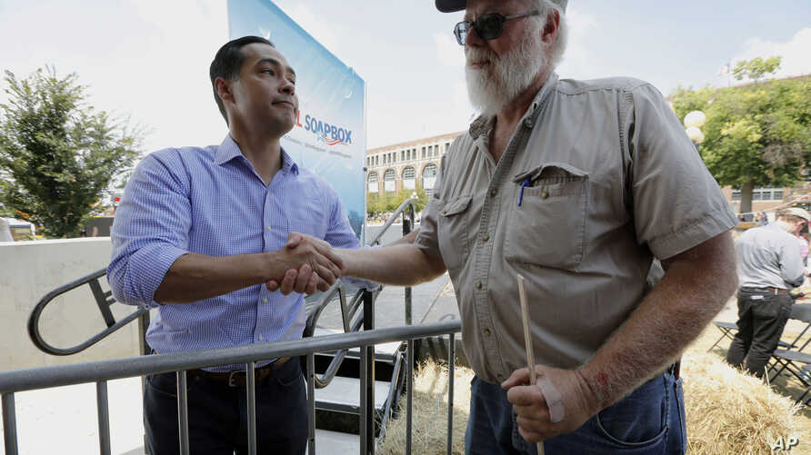 Former Housing and Urban Development Secretary Julian Castro talks with Mark Winslow, of Corydon, Iowa, right, during a visit to the Iowa State Fair, Aug. 17, 2018, in Des Moines. Castro has told Rolling Stone magazine that he's likely to run for pre