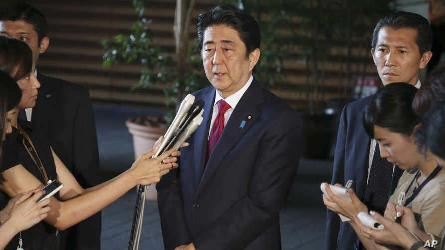 Japan's Prime Minister Shinzo Abe, center, speaks to reporters at his official residence in Tokyo, July 17, 2015.