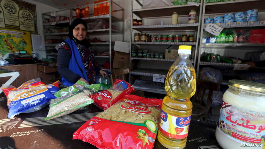 A worker sells subsidized food commodities at a government-run supermarket in Cairo, Egypt, Feb.14, 2016.