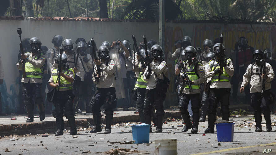 National Police stand ready to launch tear gas at student protesters outside the Central University of Venezuela in Caracas, May 4, 2017.