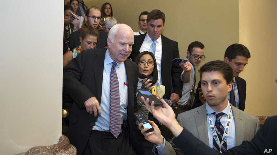 """Sen. John McCain, R-Az., front left, is pursued by reporters after casting a """"no"""" vote on a measure to repeal parts of former President Barack Obama's health care law, on Capitol Hill in Washington, July 28, 2017."""