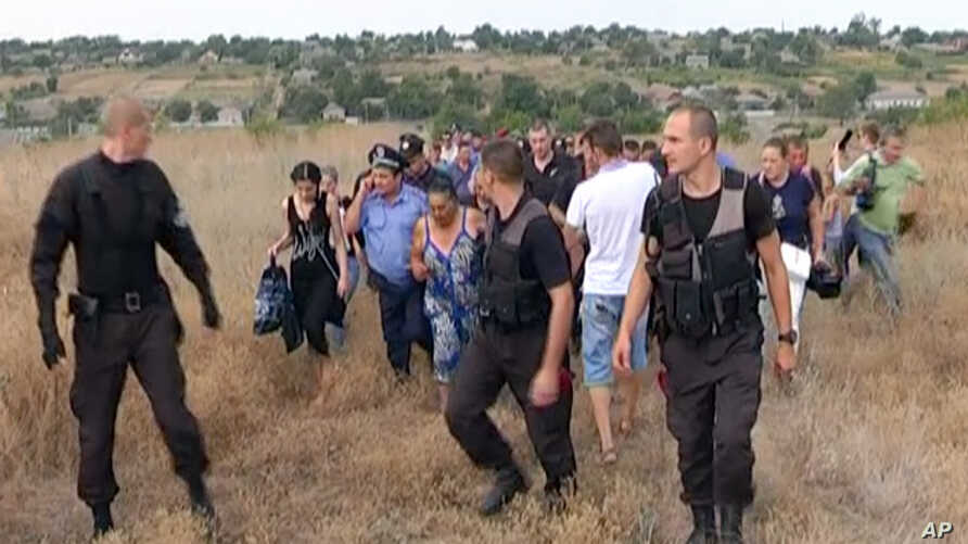 FILE - Ukrainian police officers escort the Roma residents from the village of Loshchynivka, Odessa region, Ukraine, in this image made from video taken Aug. 28, 2016. Ukrainian police evacuated a group of Roma residents from a southern town after vi