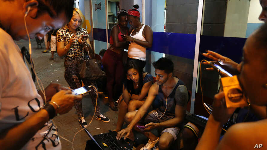 People surf the Internet at a public Wi-Fi hotspot in downtown Havana, Cuba, March 16, 2016.