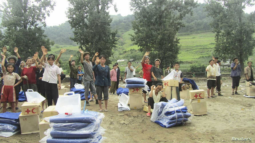 A handout photo dated July 31, 2012 shows North Korean residents waving as they receive relief goods from DPRK Red Cross Society (RCS) after rain-triggered floods hit Songchon county, South Pyongan Province.