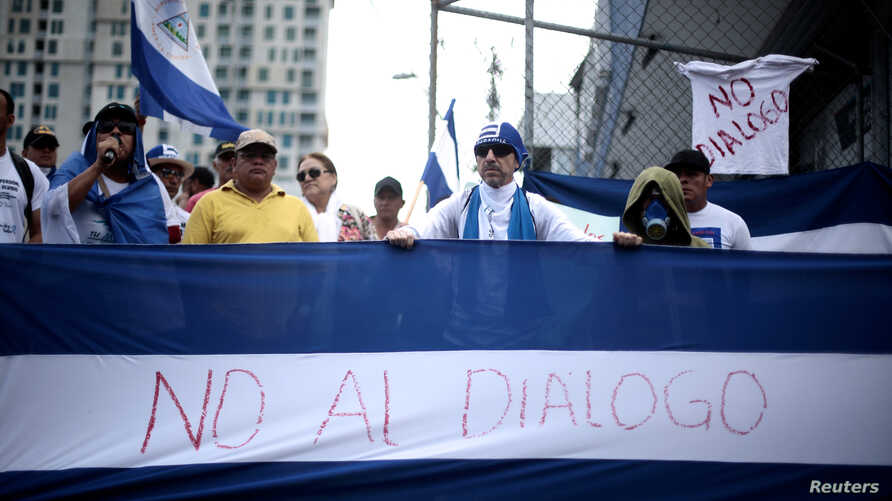 """Nicaraguans display a national flag saying """"No to dialogue"""" during a protest in San Jose, Costa Rica, against the talks their President Daniel Ortega will resume with the leaders of the opposition, Feb. 22, 2019."""