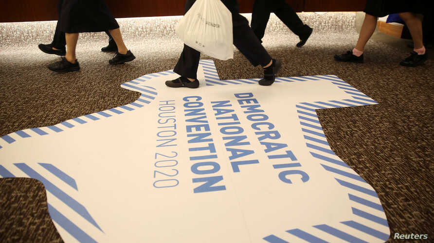 FILE - Hotel staff walk near a floor banner advertising the City of Houston's bid to host the 2020 Democratic National Convention during the Democratic National Committee (DNC) Summer Meeting in Chicago, Illinois, U.S., Aug. 23, 2018. Milwaukee has b