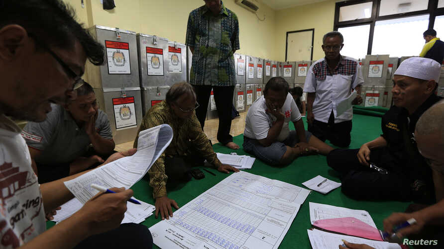 Election commission official Dedi Saidi, left, reads a document stating the number of votes collected in ballot boxes, at Bendungan Hilir, Jakarta, July 10, 2014.