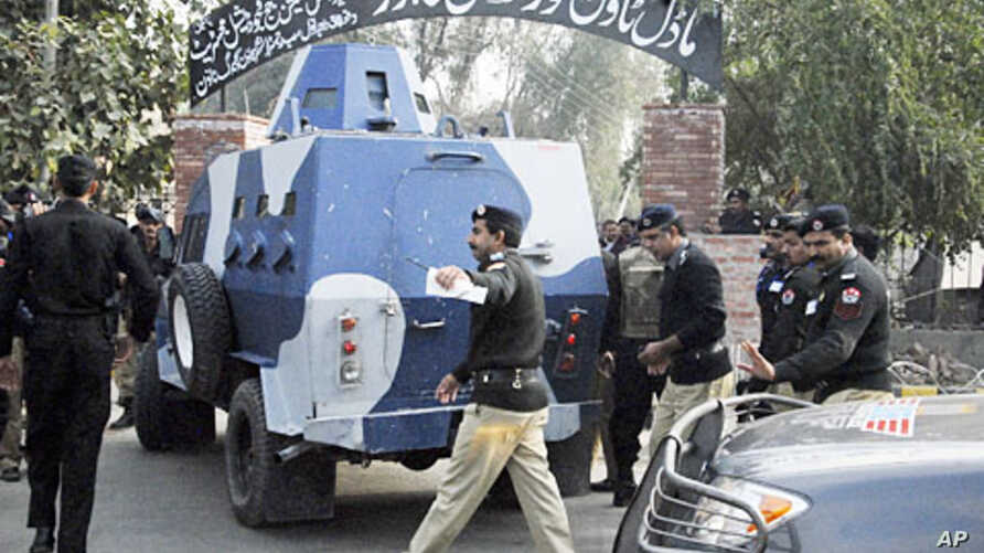 Policemen escort an Armored Personal Carrier (APC) transporting U.S national Raymond Davis as he arrives to appear before a court in Lahore, Pakistan, February 11, 2011