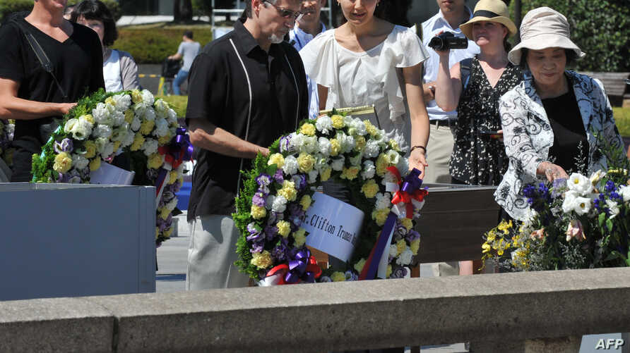 Clifton Truman Daniel (C), a grandson of former U.S. president Harry Truman, who authorized the atomic bombing of Japan during World War II, offers a wreath of flowers at the memorial cenotaph for the people killed by the atomic bomb at the Peace Mem
