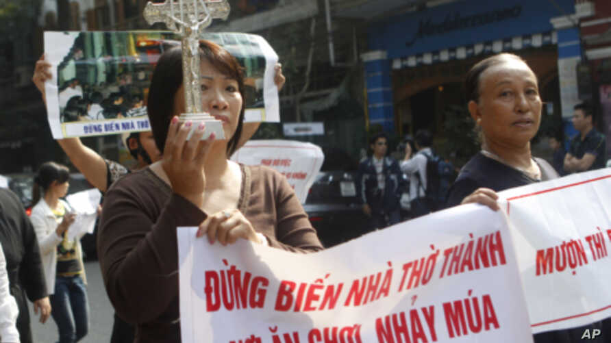 Parishioners of Thai Ha church hold a crucifix and anti-government banners while marching in Hanoi, November 18, 2011.