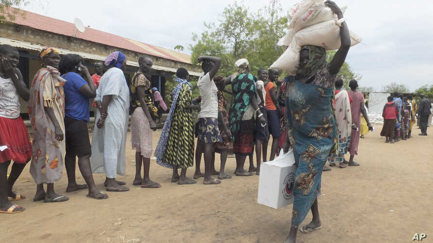 A South Sudanese woman carries food donated by Saudi Arabia Government through the Islamic Council of South Sudan in Juba, South Sudan, April 19, 2017.