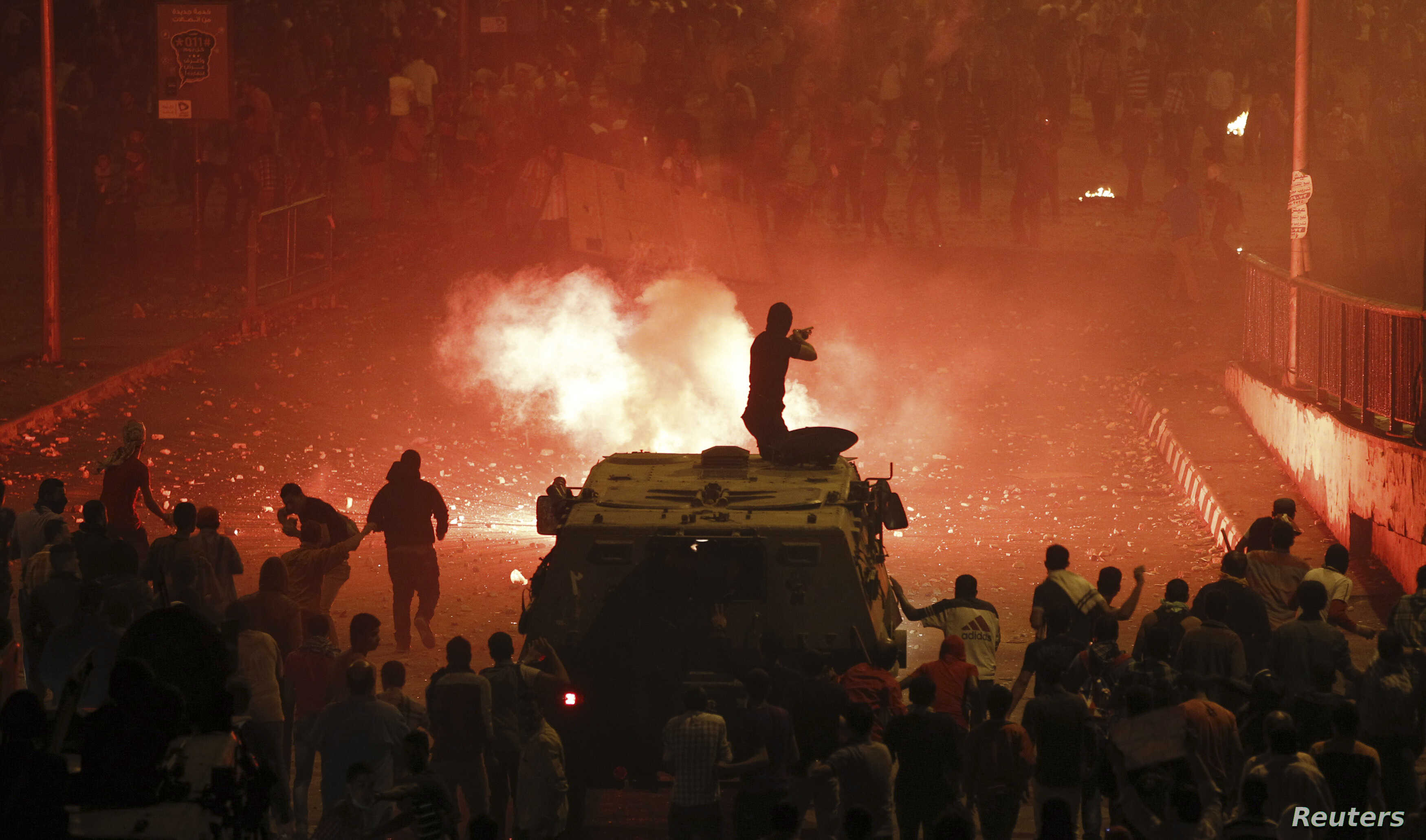 A riot police officer, on a armoured personnel carrier surrounded by anti-Morsi protesters (foreground), fires rubber bullets at members of the Muslim Brotherhood and supporters of Morsi, Oct. 6, 2013.