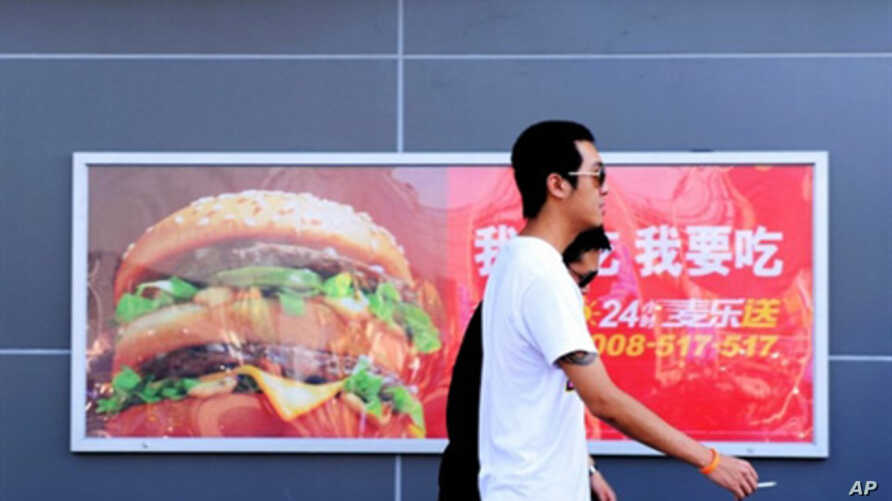Two Chinese men walk past a billboard advertising US fast-food giant McDonald's, in Yichang, central China's Hubei province, 8 July, 2010.