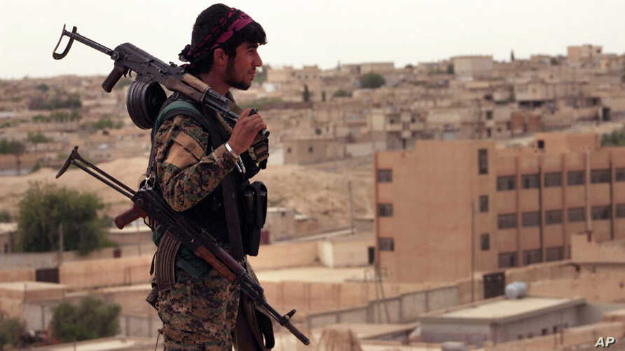 This April 30, 2017, photo provided by the Syria Democratic Forces (SDF), shows a fighter from the SDF carrying weapons as he looks toward the northern town of Tabqa, Syria.