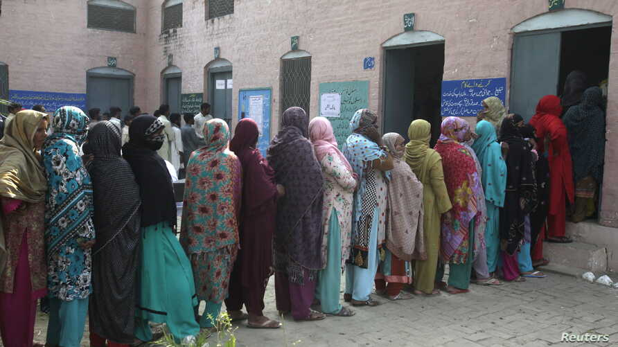 Women wait in line to vote for local government elections in Lahore, Pakistan October 31, 2015.